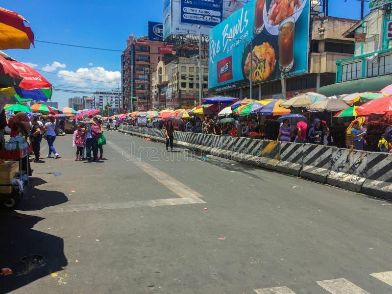 De wegkant van een nationale verkeershub in Metro Manila, overvol door mensen die verschillende objecten verkochten om een vlooie stock afbeeldingen