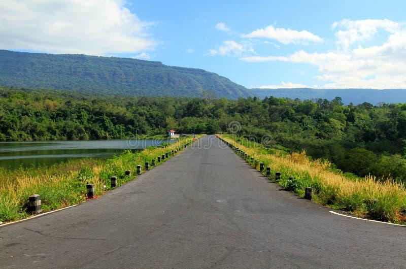 De wegrek langs een mooi rivier of een meer, met bergen, blauwe hemel, witte wolk en groene bossen in de voorgrond royalty-vrije stock foto's