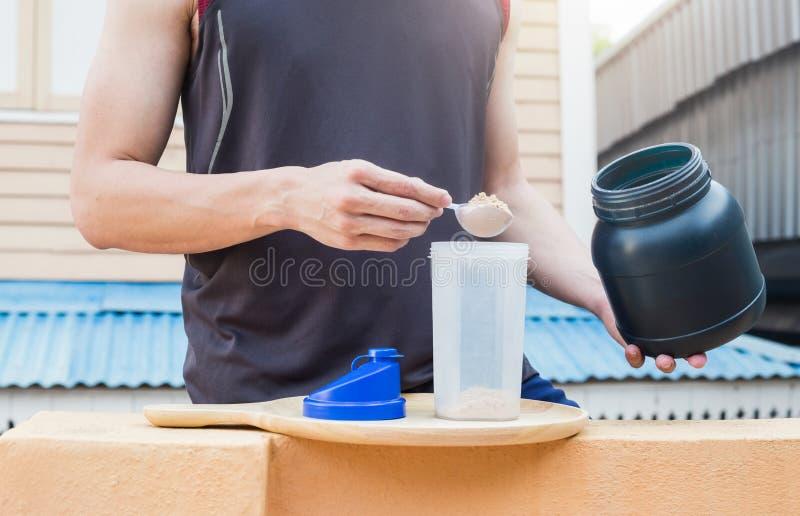 De weiproteïne, gezonde levensstijl, mens giet weipoeder op bot stock afbeelding
