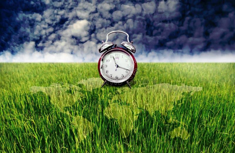 De wekker en het groene padieveld met wereld brengen bekleding, Tijd aan aanplanting in kaart royalty-vrije stock afbeelding