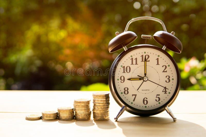 De wekker en de muntstukken met zonlicht in het park vertegenwoordigen het begin van besparingsgeld stock fotografie
