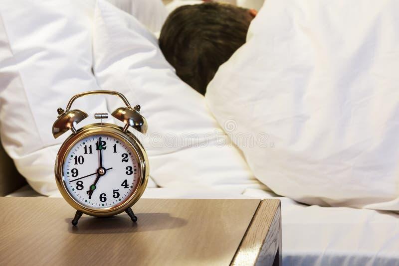 De wekker zich bevindt op een bedlijst in de ruimte of hotelruimte royalty-vrije stock fotografie