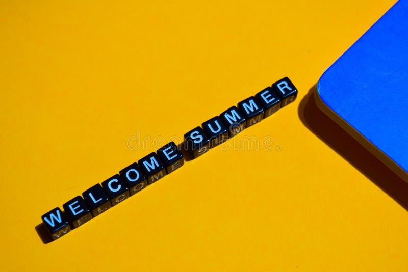 De welkom zomer op houten blokken bedrijfsconcept op oranje achtergrond stock fotografie