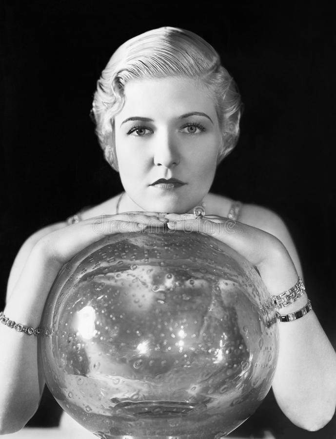De wereld zou haar oester kunnen zijn, maar deze jonge vrouw schijnt, leunend op haar kristallen bol (Alle afgeschilderde persone royalty-vrije stock foto's