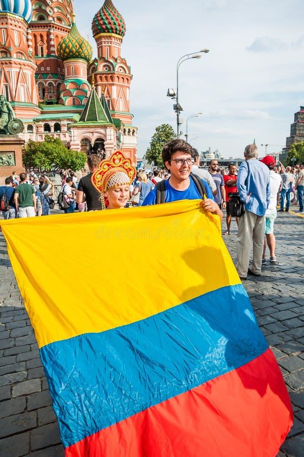 De Wereldbeker van FIFA van 2018 Columbiaanse ventilator met vlag en meisje in Russisch nationaal die hoofddeksel kokoshnik op Ro stock afbeeldingen