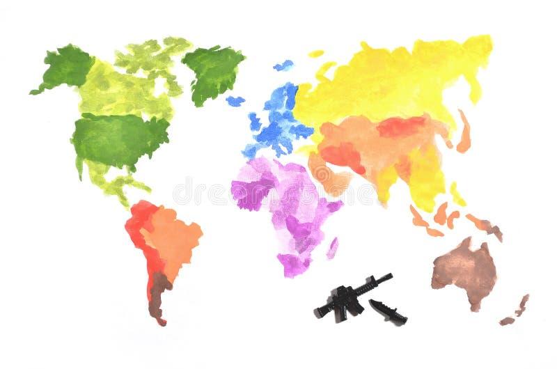 De wereldkaart wordt gemaakt met gekleurde waterverfverven op Witboek met de participatie van een zwart stuk speelgoed kanon en e stock foto