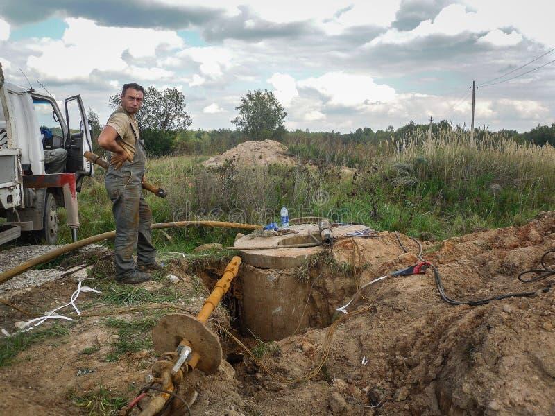 De werken bij het leggen van watervoorziening op plattelandsgebieden in het Kaluga-gebied in Rusland royalty-vrije stock foto