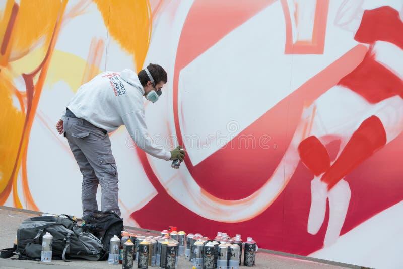 De werken van de graffitikunstenaar aangaande zijn verwezenlijking stock foto