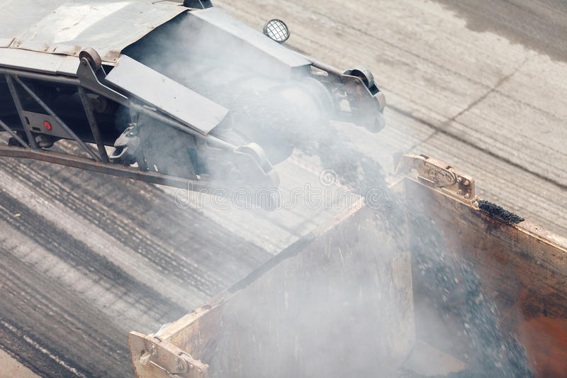 De werken van de weg Asfalt die machinelading gepoederd asfalt op de vrachtwagen verwijderen stock afbeeldingen