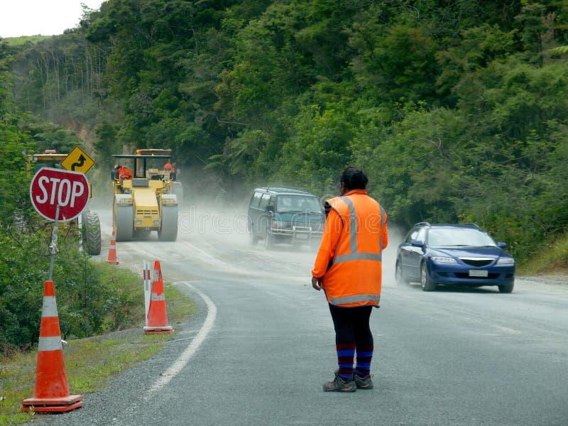 De werken van de weg: vrouwen arbeider met eindeteken en auto's stock foto