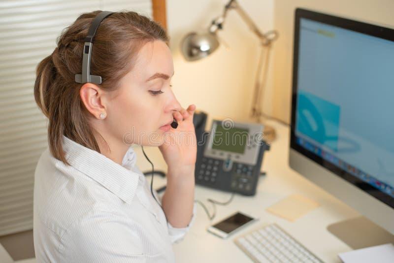 De werken van de meisjesverzender met de telefoon In het call centre stock afbeelding