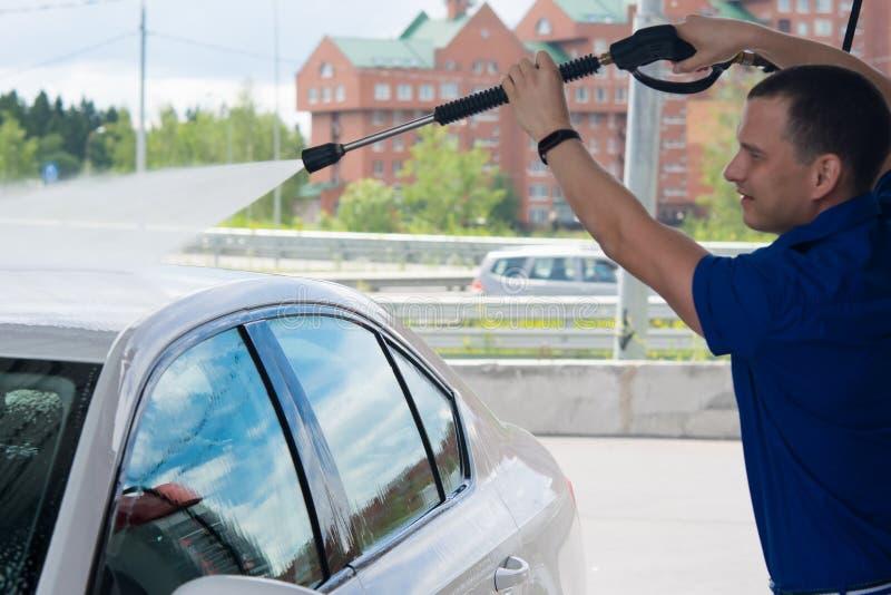 De werkende mens wast de auto onder hoge druk royalty-vrije stock foto's