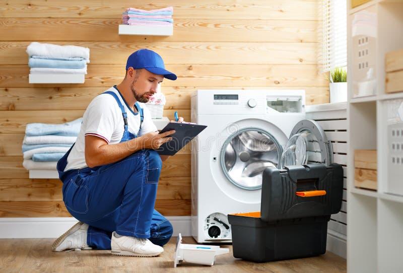 De werkende mensenloodgieter herstelt wasmachine in wasserij royalty-vrije stock afbeelding