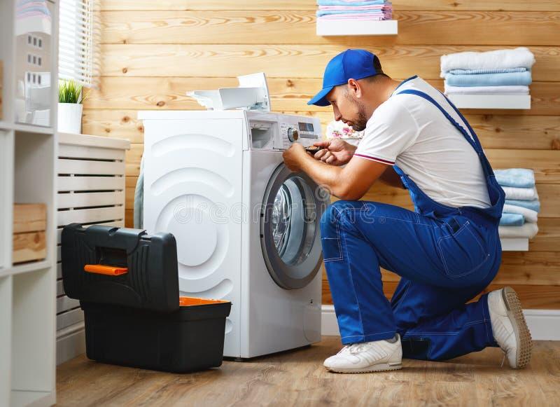 De werkende mensenloodgieter herstelt wasmachine in wasserij stock afbeelding