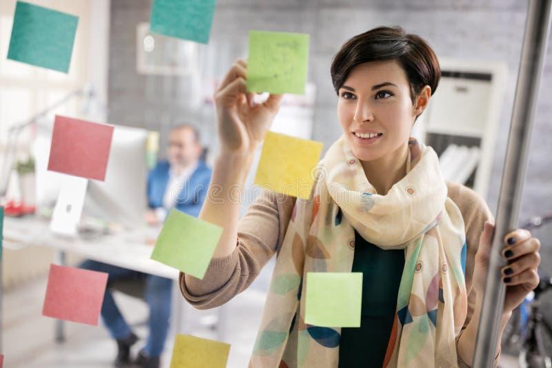 De werkende vrouw maakt regeling op stickers op het werk stock foto's