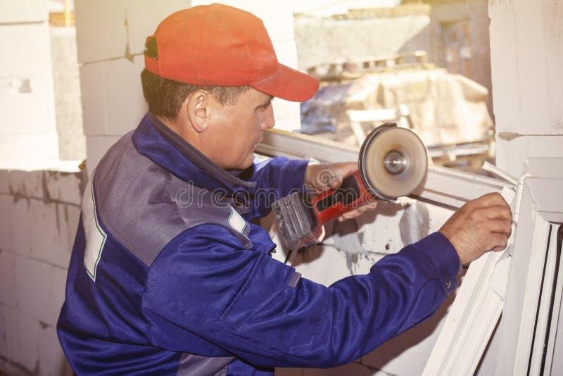 De werkende werkende zagen die van het installatie plastic venster een huis bouwen stock afbeeldingen