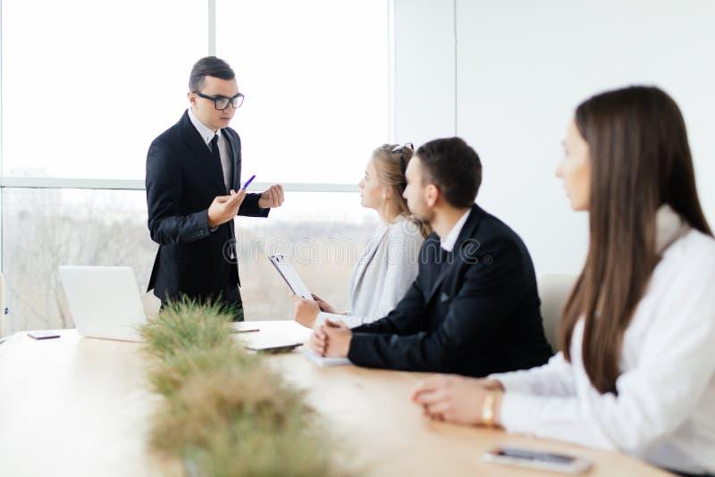 De werkgever in formalwear verklaart en besprekend iets terwijl het zitten samen bij de lijst royalty-vrije stock afbeeldingen