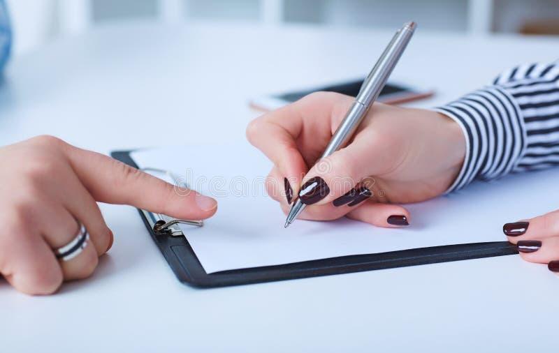 De werkgever maakt de werknemer om een brief van berusting te schrijven stock foto