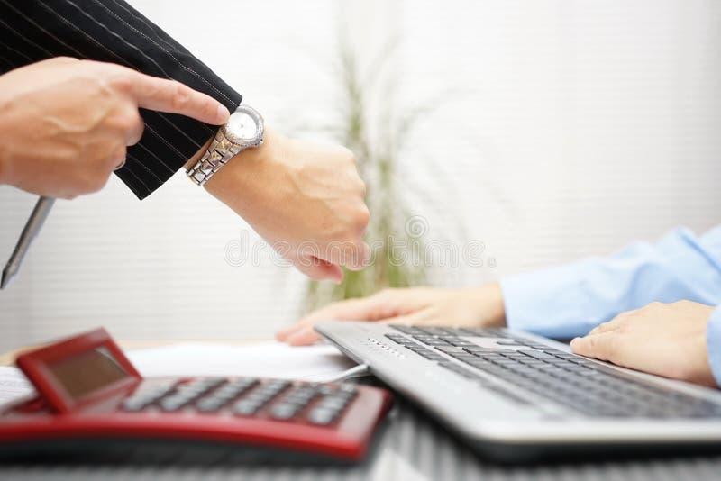 De werkgever richt aan het horloge, is hij laat met het werk, druk stock afbeelding