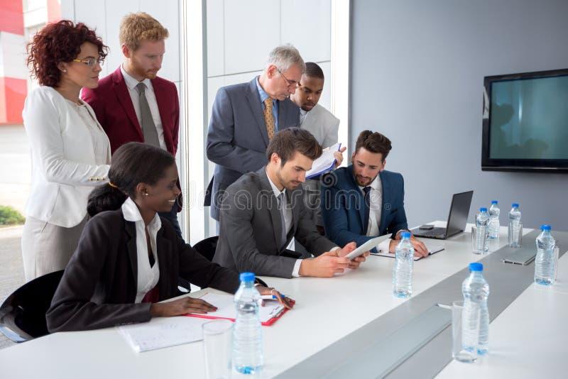 De werkgever volgt gegevens van tablet in bedrijfvergadering stock afbeeldingen