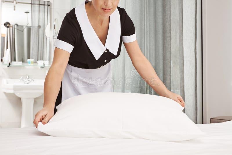 De werkgever zal met resultaat worden tevredengesteld Bebouwd schot van dienstmeisje schoonmakende slaapkamer, makend bed en slaa stock afbeeldingen