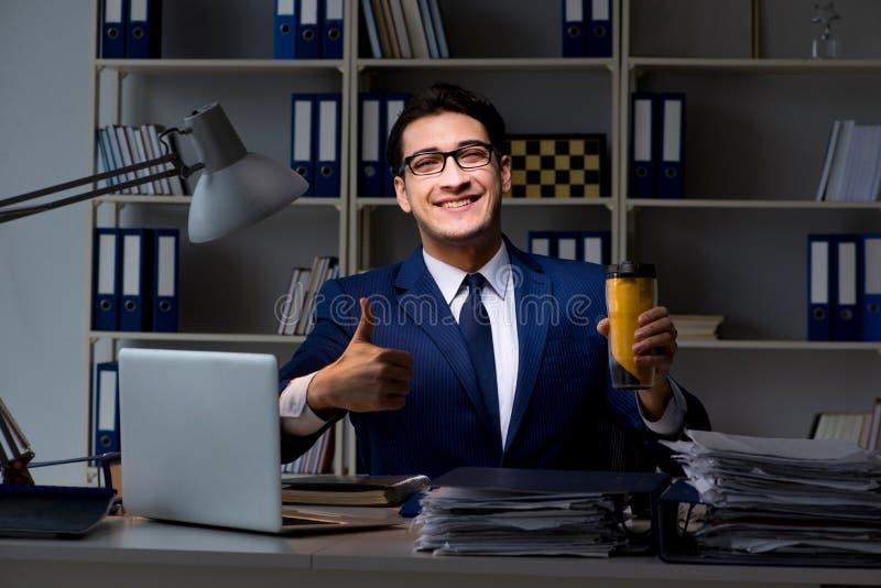 De werknemer laat en het drinken sterke koffie die om wakker te blijven werken royalty-vrije stock afbeeldingen