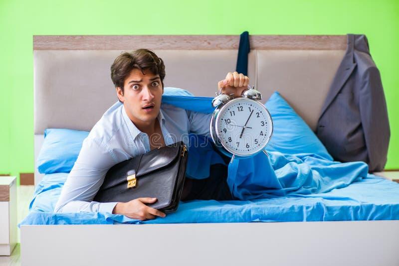 De werknemer in de slaapkamer die laat voor zijn baan managemen op tijd zijn stock afbeeldingen