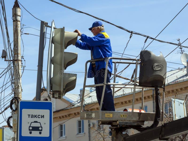 De werknemer van de stadsdiensten dient een verkeerslicht op het gebied van Lenin ` s van de stad van Voronezh stock foto's