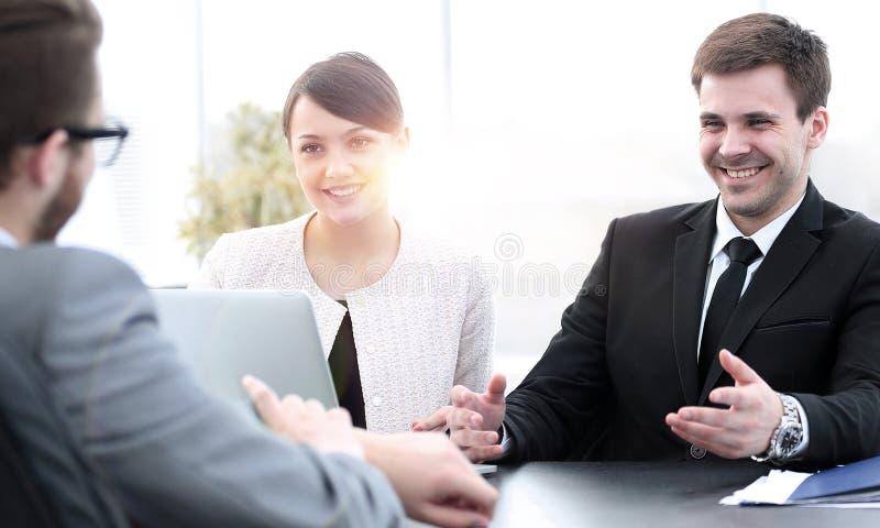 De werknemers communiceren met de klant in het bureau stock fotografie