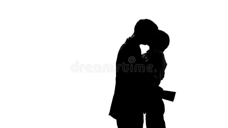 De werknemers silhouetteert passionately het koesteren en het kussen in bureauminnaars het bedriegen stock fotografie
