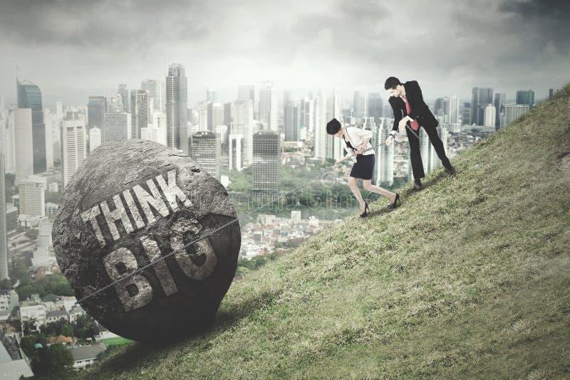 De werknemers trekken steen met Think Groot woord royalty-vrije stock fotografie