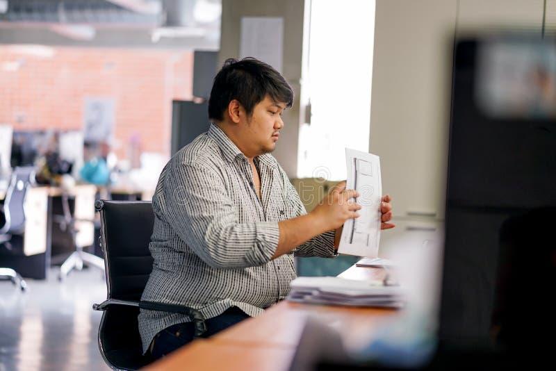 De werknemersmens bereidt documenten in het bureau voor Met het Binden van Machine stock foto