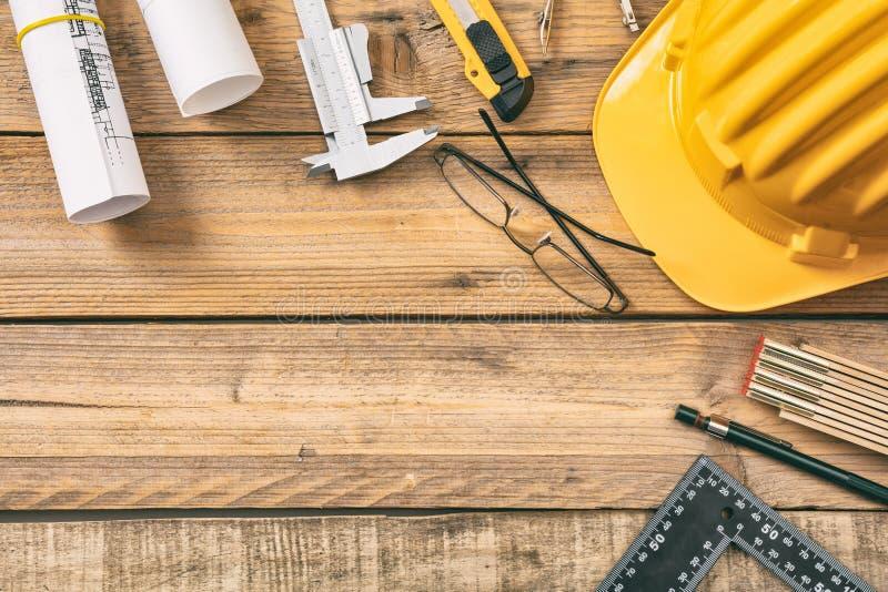 De werkplaats van de architect De blauwdrukken van de projectbouw en techniekhulpmiddelen op houten bureau, exemplaarruimte stock foto