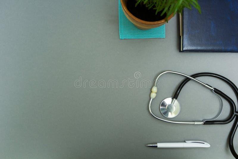 De werkplaats van de arts Blocnote met pen, stethoscoop en bloempot op een grijze achtergrond stock fotografie