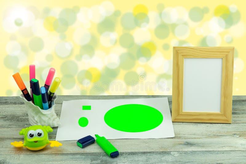 De werkplaats van kind schildert een beeld en een leeg houten kader over heldere bokehachtergrond Ruimte voor youHappy kinderenda stock afbeeldingen