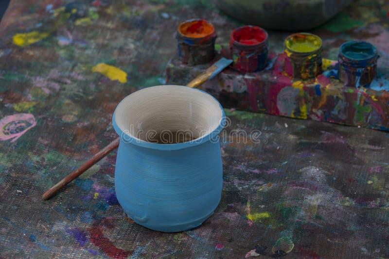 De werkplaats van de pottenbakker met unpainted ambachtvaas, aardewerkverven, en borstel De achtergrond van het hobbyconcept voor stock afbeeldingen