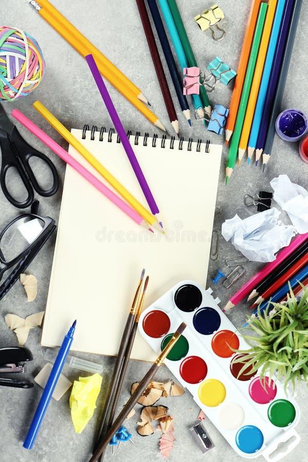 De werkplaatssamenstelling met verf, notitieboekje en kleurenpotloden op vlakke lijst, legt royalty-vrije stock fotografie