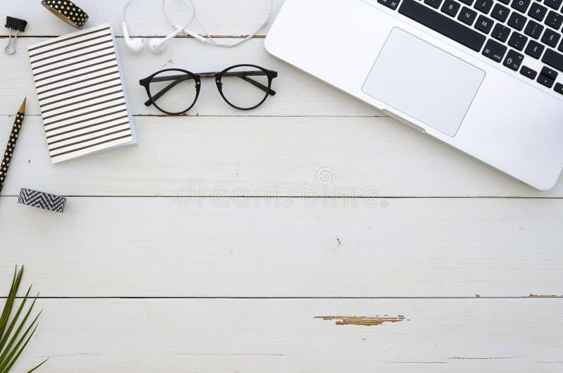 De werkruimte van het huisbureau met laptop, glazen, palmblad, earpligs, notitieboekje en bureautoebehoren Vlak leg, hoogste meni stock foto