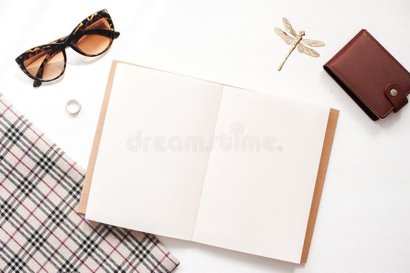 De werkruimtemodel van het huisbureau met vrouwenglazen, portefeuille en vrouwentoebehoren Notitieboekje met blanco pagina's De h stock fotografie