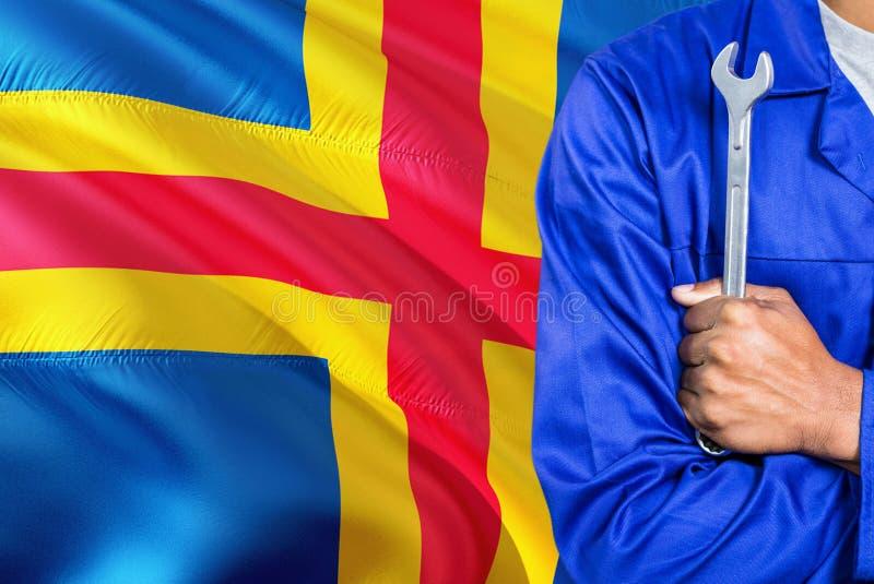 De werktuigkundige in blauwe eenvormig houdt moersleutel tegen de golvende Aland-achtergrond van de Eilandenvlag Gekruiste wapens royalty-vrije stock afbeeldingen