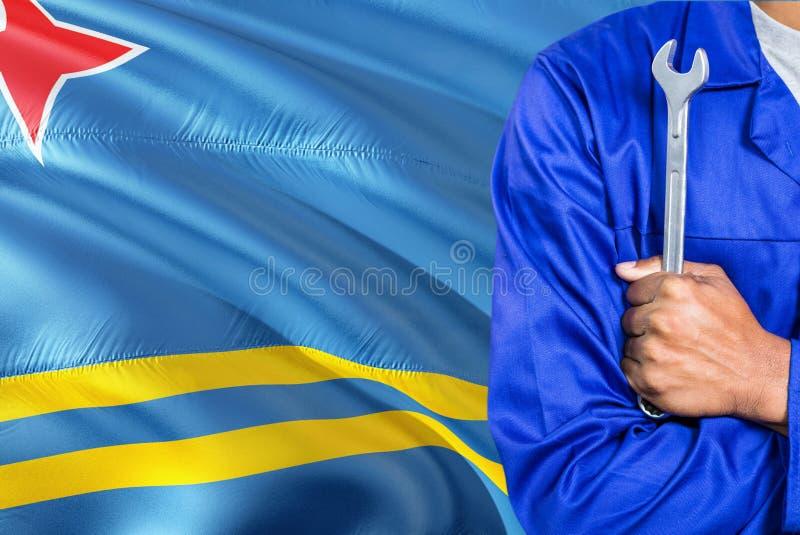 De werktuigkundige in blauwe eenvormig houdt moersleutel tegen golvende de vlagachtergrond van Aruba Gekruiste wapenstechnicus stock afbeeldingen