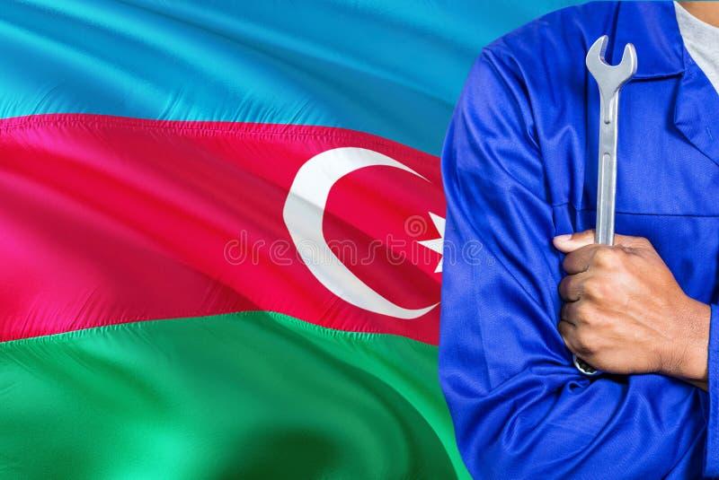De werktuigkundige in blauwe eenvormig houdt moersleutel tegen golvende de vlagachtergrond van Azerbeidzjan Gekruiste wapenstechn stock foto's