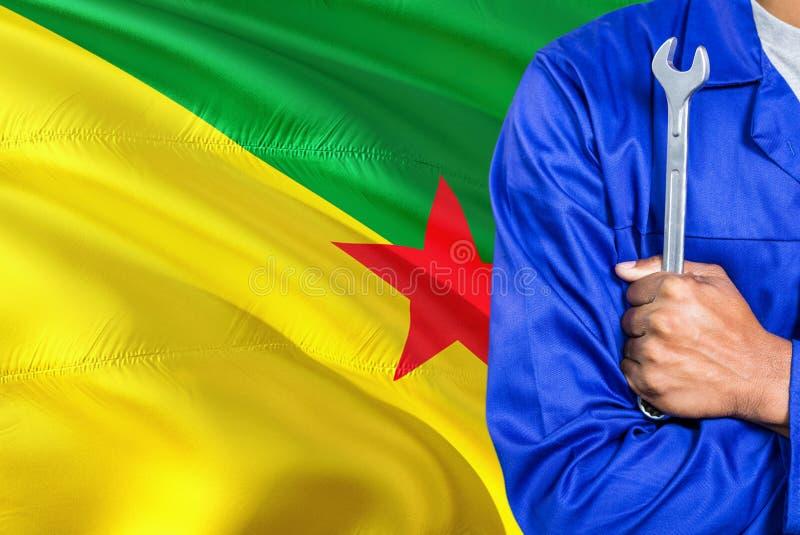 De werktuigkundige in blauwe eenvormig houdt moersleutel tegen golvende de vlagachtergrond van Frans-Guyana Gekruiste wapenstechn stock foto's