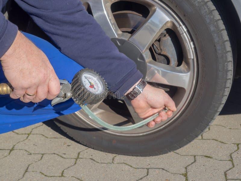 De werktuigkundige controleert de druk van de bandinflatie van een auto stock fotografie