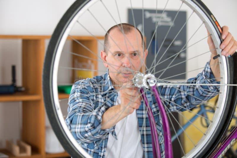 De werktuigkundige die van de mensenfiets fietsen herstellen stock afbeeldingen