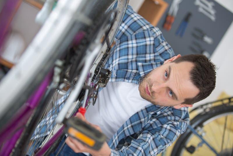 De werktuigkundige die van de mensenfiets fietsen herstellen stock afbeelding