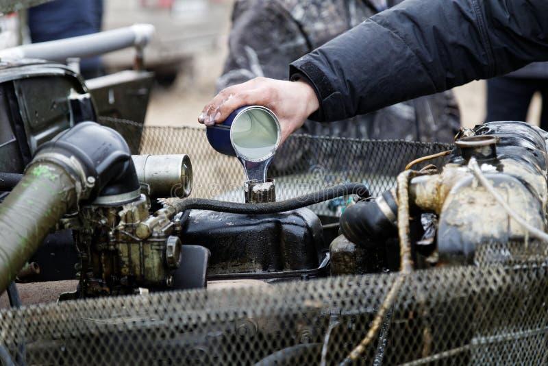 De werktuigkundige giet het additief van de motorolie in oude motor stock afbeeldingen