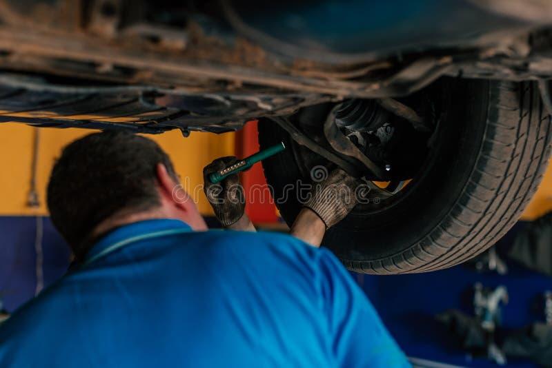 De werktuigkundige herstelt de auto van onderaan en toont de bestuurder royalty-vrije stock foto