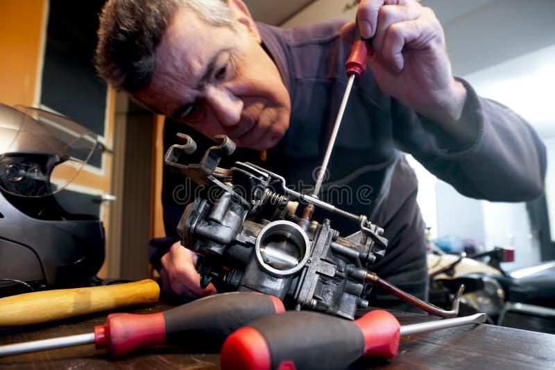 De werktuigkundige herstelt een carburator royalty-vrije stock afbeelding