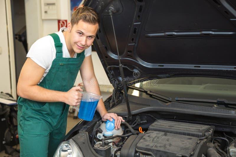De werktuigkundige vult koelmiddel of koelvloeistof in motor van een auto stock afbeeldingen